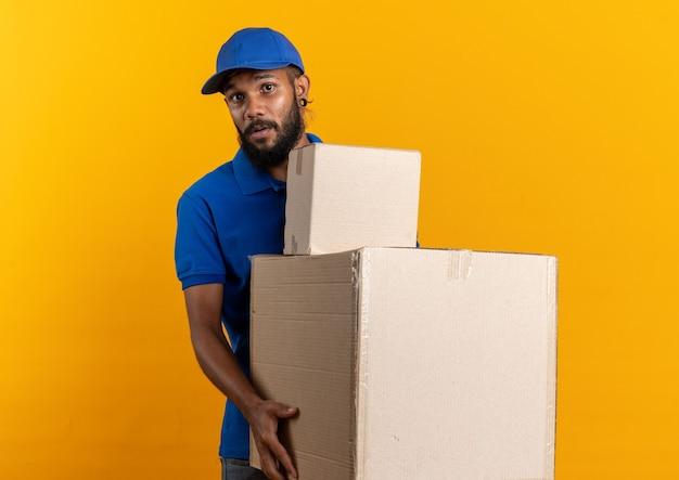 Ansioso giovane fattorino che tiene scatole di cartone isolate sulla parete arancione con spazio di copia