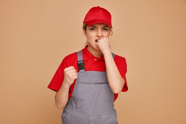 Обеспокоенная молодая женщина-строитель в кепке и униформе сжимает кулак и кусает другой кулак