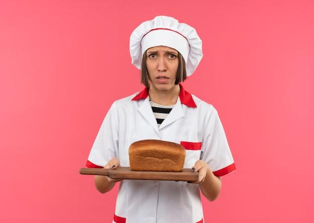 Ansioso giovane cuoco femminile in uniforme del cuoco unico che tiene tagliere con pane su di esso isolato su rosa con copia spazio