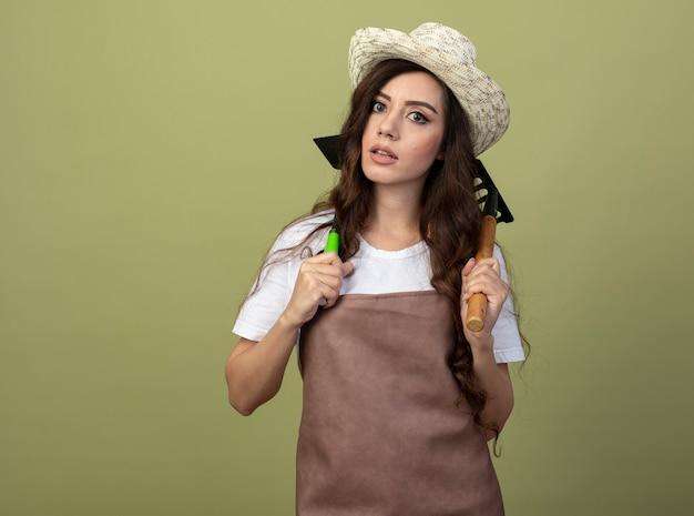 Обеспокоенная молодая женщина-садовник в униформе в садовой шляпе держит грабли и грабли на плечах, изолированные на оливково-зеленой стене