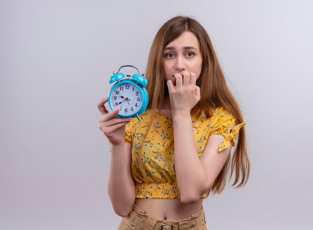 Обеспокоенная молодая девушка держит будильник и кладет руку в рот с копией пространства