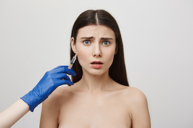 Anxious young girl making injection of botox