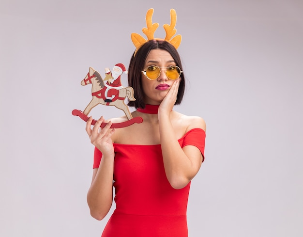 Anxious young girl wearing reindeer antlers headband and glasses holding santa on rocking horse figurine looking at camera keeping hand on face isolated on white background with copy space