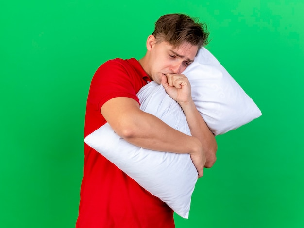 Anxious young handsome blonde ill man hugging pillow and caughing isolated on green wall