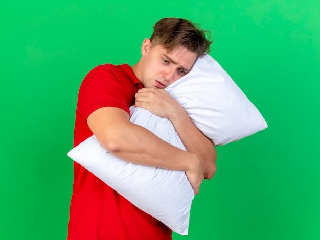 Ansioso giovane bello biondo malato abbracciando cuscino guardando verso il basso isolato sulla parete verde