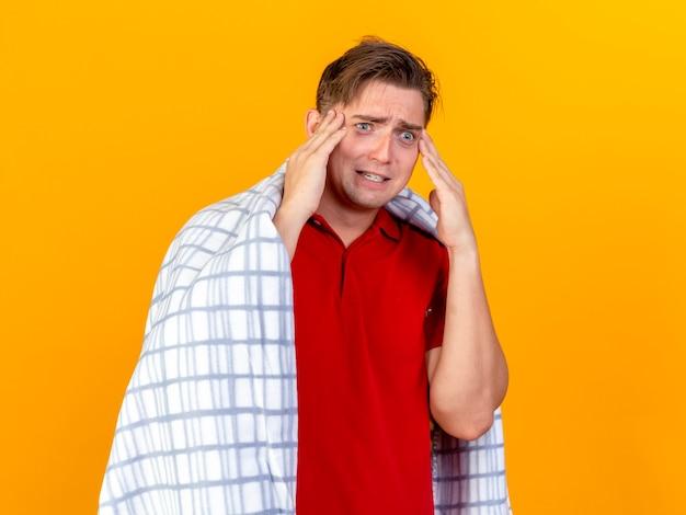 オレンジ色の壁にまっすぐに孤立しているように見える格子縞の触れる頭に包まれた気になる若いハンサムな金髪の病気の男
