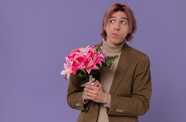 Ansioso giovane bell'uomo che tiene un mazzo di fiori e guarda di lato
