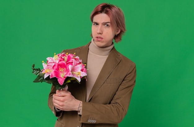 Anxious young handsome man holding bouquet of flowers and looking