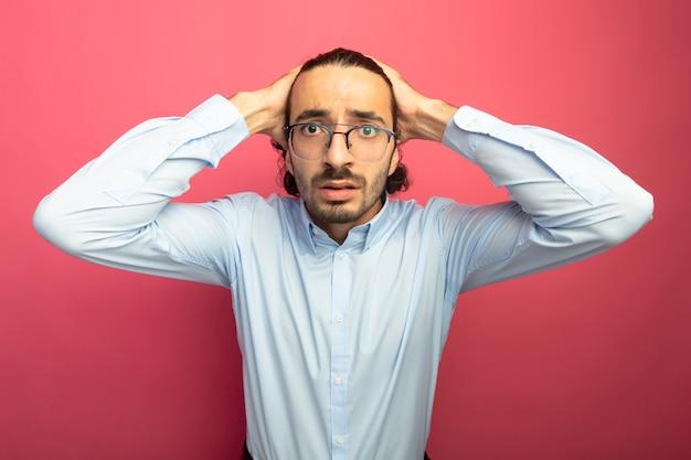 Ansioso giovane uomo bello con gli occhiali tenendo le mani sulla testa guardando la parte anteriore isolata sul muro rosa