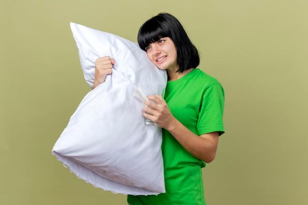 Ansioso giovane ragazza caucasica malata che tiene il cuscino guardando dritto con un bicchiere d'acqua in mano isolato sulla parete verde oliva con lo spazio della copia