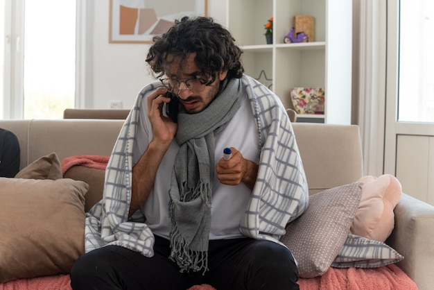 Ansioso giovane uomo caucasico malato in occhiali ottici avvolto in plaid con sciarpa intorno al collo parlando al telefono e tenendo il termometro seduto sul divano in soggiorno