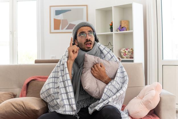 Встревоженный молодой больной человек в оптических очках, завернутый в плед, с шарфом на шее, в зимней шапке, обнимает подушку, смотрит и указывает вверх, сидя на диване в гостиной