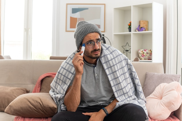 Ansioso giovane malato in occhiali ottici avvolto in plaid indossando cappello invernale tenendo il termometro guardando di lato seduto sul divano in soggiorno