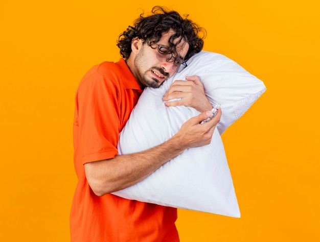 Anxious young ill man wearing glasses hugging pillow touching face with it holding pack of medical tablets looking at it isolated on orange wall