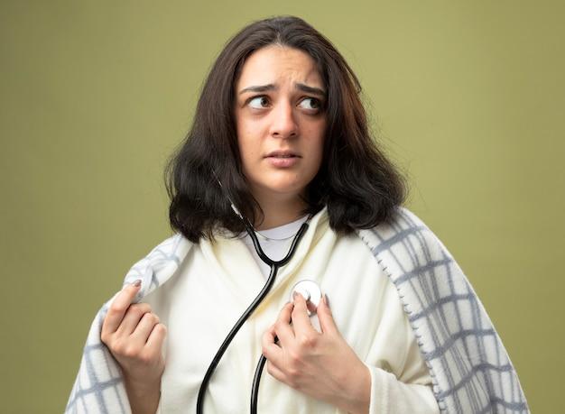 Ansiosa giovane donna malata che indossa veste e stetoscopio avvolto in un plaid ascoltando il suo battito cardiaco afferrando il plaid guardando il lato isolato sul muro verde oliva