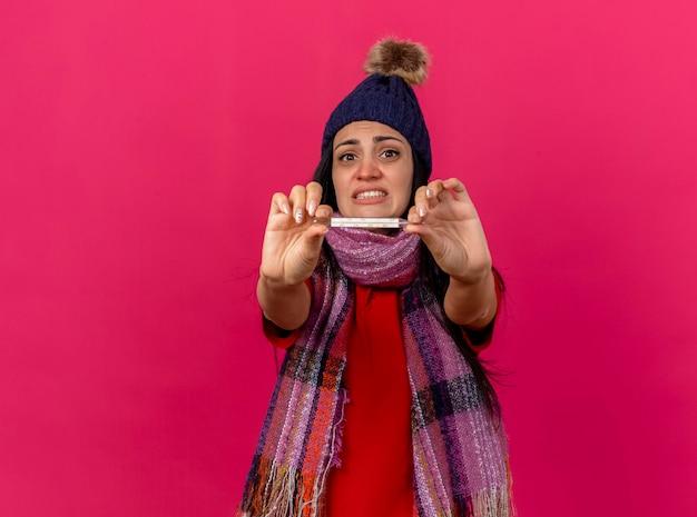 冬の帽子とスカーフを身に着けている気になる若い病気の女性は、コピースペースでピンクの壁に隔離された正面を見て温度計を正面に伸ばしています