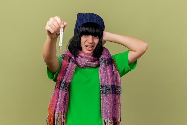 Тревожная молодая больная женщина в зимней шапке и шарфе протягивает термометр вперед, положив руку на голову, глядя вперед, изолированную на оливково-зеленой стене