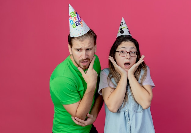 Anxious young man wearing party hat puts hand on chin looking down and standing with shocked young girl wearing party hat holding hands on chin isolated on pink wall