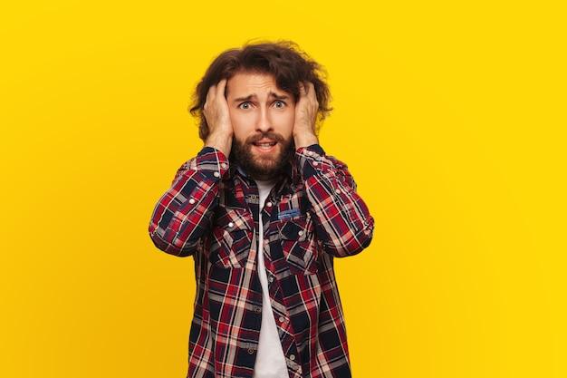 長い髪の気になる若い男が頭を抱えている。男は頭を抱えて心配している。黄色の背景