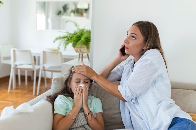 Anxious young mom call ambulance doctor take care of sick small girl child having flu and high temperature. worried mother contact therapist or pediatrician with little daughter feel ill.