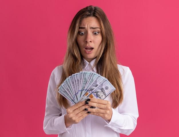 La giovane ragazza piuttosto caucasica ansiosa tiene e guarda i soldi isolati sulla parete rosa con lo spazio della copia