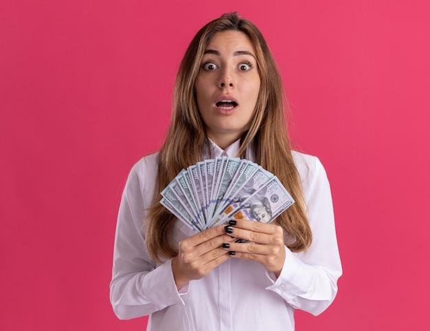 La giovane ragazza abbastanza caucasica ansiosa tiene i soldi isolati sulla parete rosa con lo spazio della copia