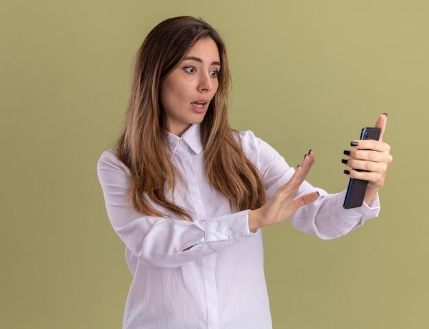 Тревожная молодая симпатичная кавказская девушка смотрит и протягивает руку к телефону