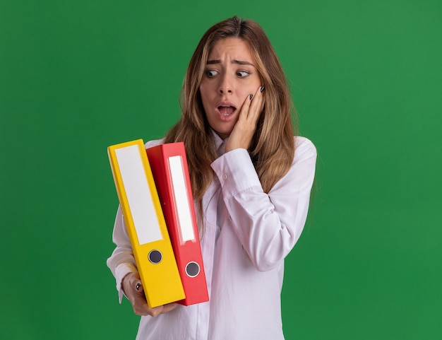 Anxious young pretty caucasian girl puts hand on face holding and looking at file folders on green