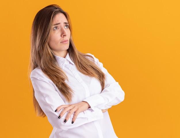 Тревожная молодая симпатичная кавказская девушка стоит со скрещенными руками, глядя в сторону, изолированную на оранжевой стене с копией пространства