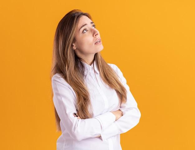 Тревожная молодая симпатичная кавказская девушка стоит со скрещенными руками, глядя вверх изолированно на оранжевой стене с копией пространства