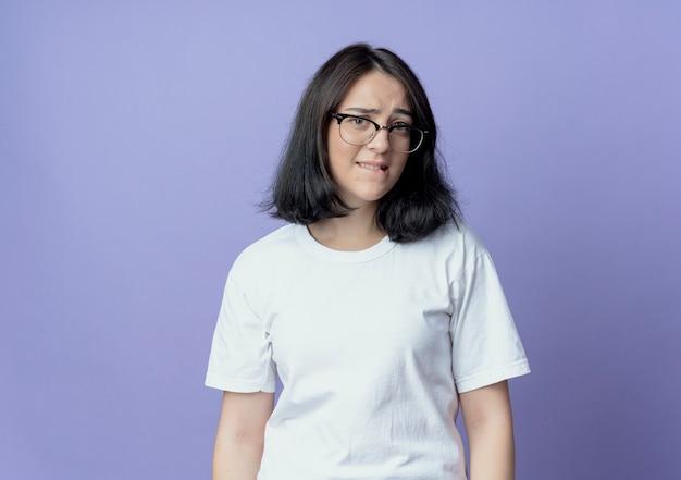 コピースペースと紫色の背景に分離された唇を噛む眼鏡をかけている気になる若いかなり白人の女の子