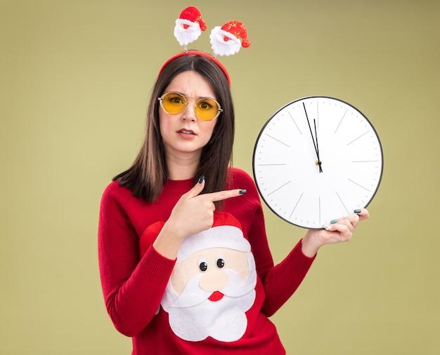 산타 클로스 스웨터와 안경 들고 올리브 녹색 배경에 고립 된 카메라를보고 시계를 가리키는 머리띠를 착용하는 불안 젊은 예쁜 백인 여자