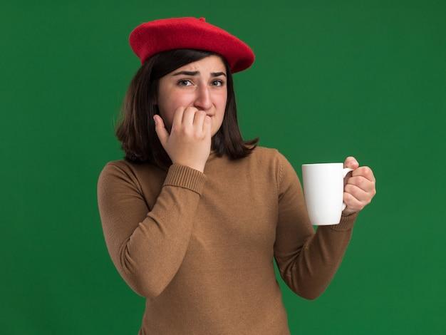 ベレー帽の帽子をかぶった気になる若いかなり白人の女の子が爪を噛み、緑のカップを保持