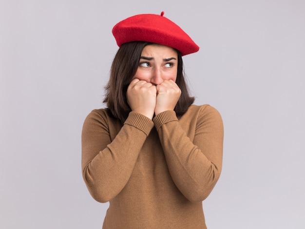Ansiosa giovane bella ragazza caucasica con berretto mette i pugni sul mento e guarda di lato
