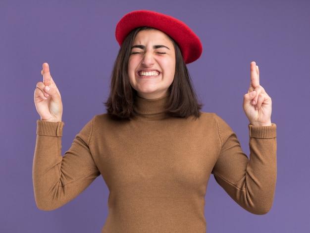 ベレー帽の帽子をかぶった気になる若いかなり白人の女の子は、コピースペースと紫色の壁に分離された腕を組んで立っています