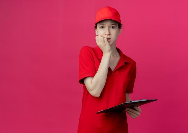 カメラを見て、コピースペースで深紅色の背景に分離された指を噛むクリップボードを保持している赤い制服と帽子の気になる若いかわいい配達の女の子