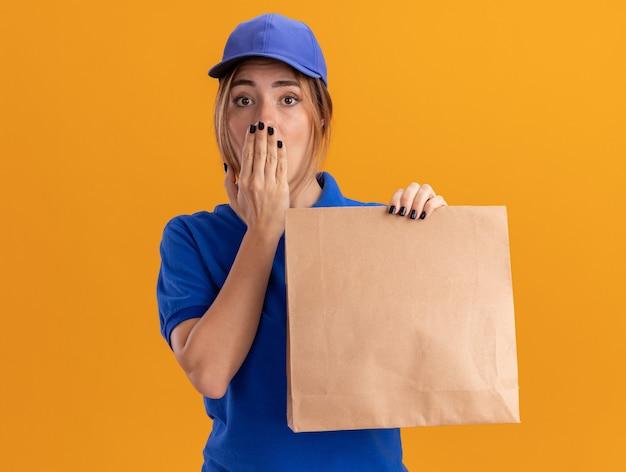 Обеспокоенная молодая симпатичная доставщица в униформе кладет руку на рот и держит бумажный пакет на оранжевом