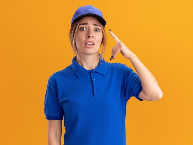 Ansioso giovane bella ragazza di consegna in uniforme indica su arancione