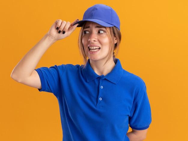 Ansiosa giovane bella ragazza di consegna in uniforme mette la mano sul berretto e guarda a lato su arancione