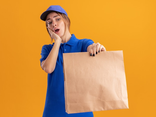 Ansioso giovane bella ragazza di consegna in uniforme mette la mano sul viso tenendo e guardando il pacchetto di carta sull'arancio