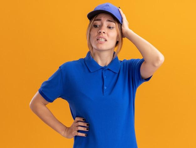 Ansiosa giovane bella ragazza di consegna in uniforme mette la mano sulla testa e guarda verso il basso sull'arancia