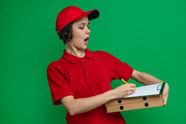 Ansiosa giovane graziosa donna di consegna che tiene e guarda gli appunti sulle scatole della pizza