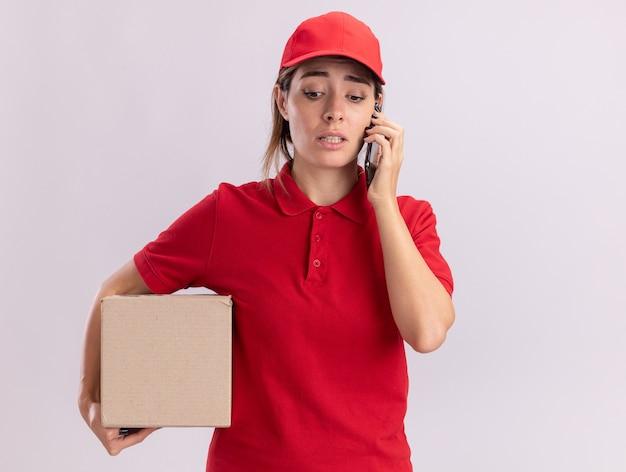 Тревожная молодая красивая женщина-доставщик в униформе держит картонную коробку и разговаривает по телефону, изолированному на белой стене