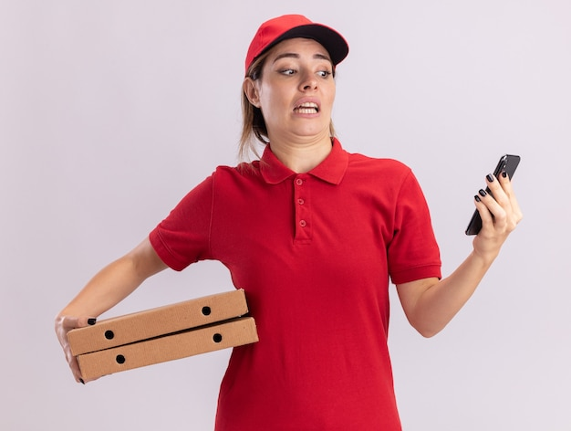 制服を着た気になる若いかわいい配達の女性はピザの箱を保持し、分離された電話を見て