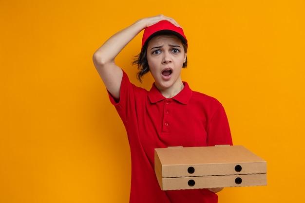 Тревожная молодая красивая женщина-доставщик кладет руку ей на голову и держит коробки для пиццы