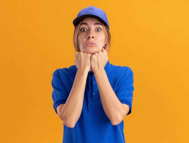 Ansiosa giovane donna graziosa di consegna in uniforme mette i pugni sul mento e guarda davanti isolato sulla parete arancione