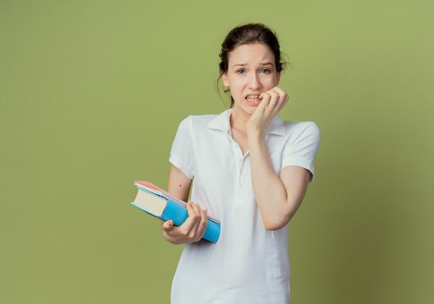 本とメモ帳を保持し、コピースペースでオリーブグリーンの背景に分離された指を噛む気になる若いきれいな女性の学生