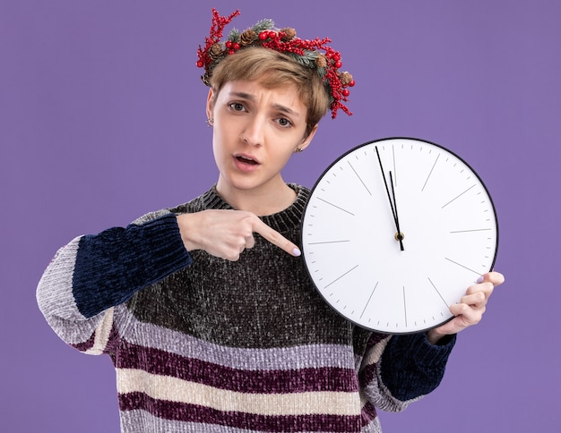 紫色の背景に分離されたカメラを見て時計を保持し、指しているクリスマスの頭の花輪を身に着けている気になる若いかわいい女の子