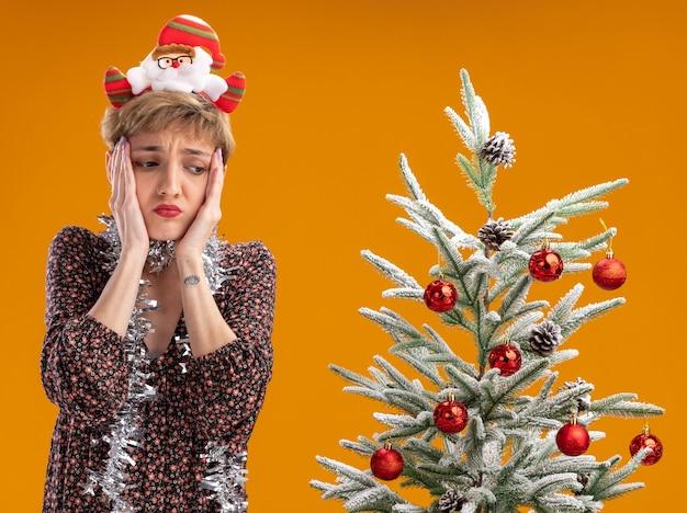 サンタクロースのヘッドバンドと首の周りに見掛け倒しの花輪を身に着けている気になる若いかわいい女の子は、オレンジ色の背景で隔離された顔を見下ろしている装飾されたクリスマスツリーの近くに立っています