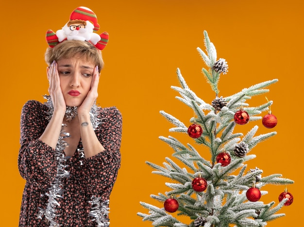 Anxious young pretty girl wearing santa claus headband and tinsel garland around neck standing near decorated christmas tree keeping hands on face looking down isolated on orange background